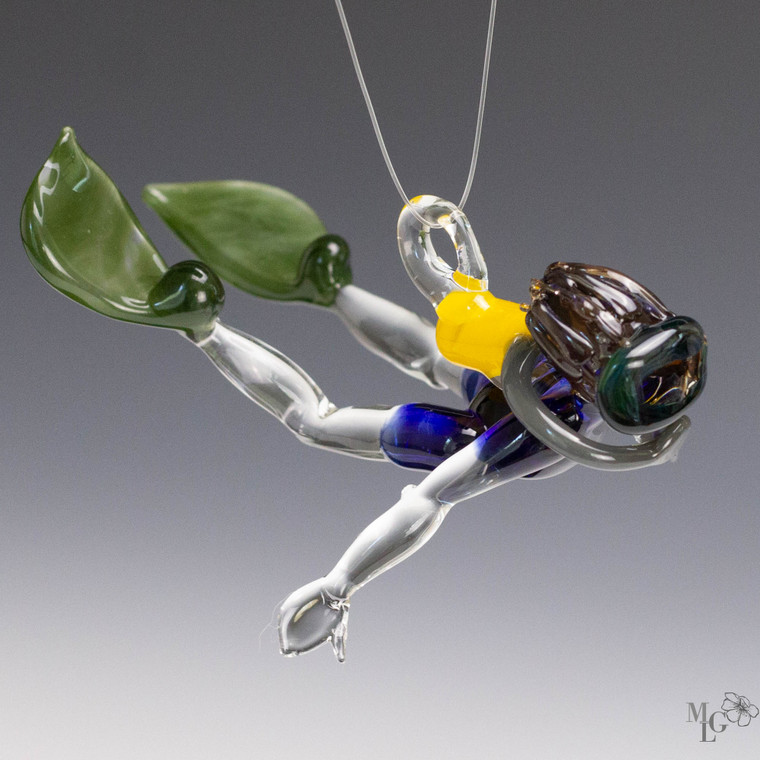 Scuba Dude - Jeffrey  Fun glass ornament. He has medium brown hair that is translucent so it sparkles in the sun  His mask is an interesting color. Sometimes it looks like a smokey charcoal grey. Sometimes you can see the rain forest green.