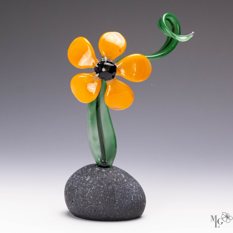 Orange glass flower sculpture with curly green stem  The rock bottom is an artisan crafted faux stone
