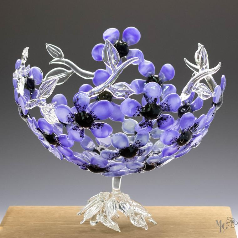 Stunning periwinkle glass flowers arranged in an open basket design