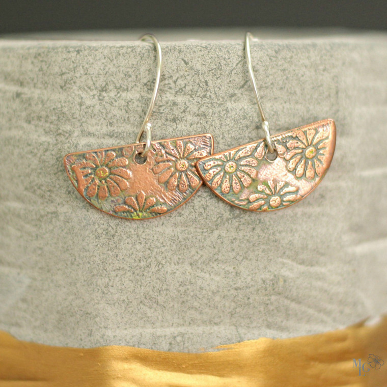 Antiqued copper earrings with a daisy flower design. They have been hand rubbed with bits of color. There is faint yellow in the center of the daisies and greenish finish around edges of the flowers.