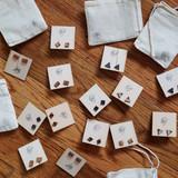 Earring studs on wooden card in muslin bag