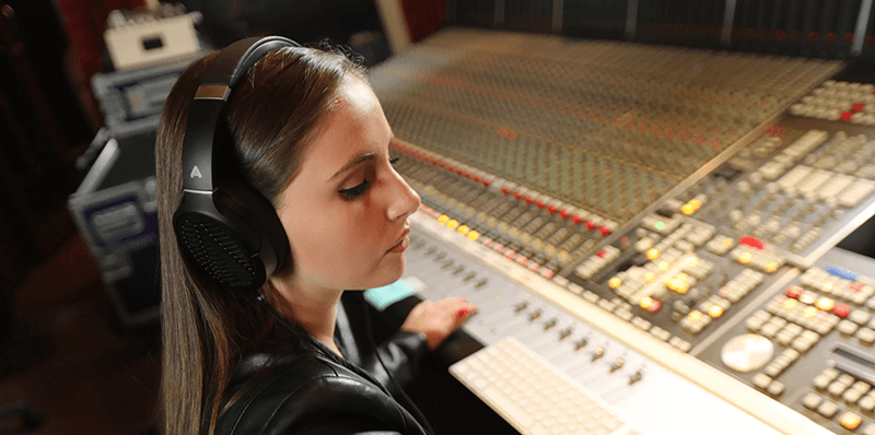 young woman wearing LCD-1 headphones at a mixing board