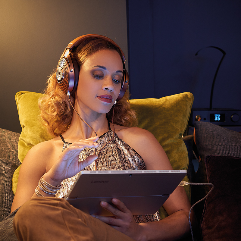 Woman on sofa wearing Focal Stellia Headphones with a tablet and Focal Arche amplifier