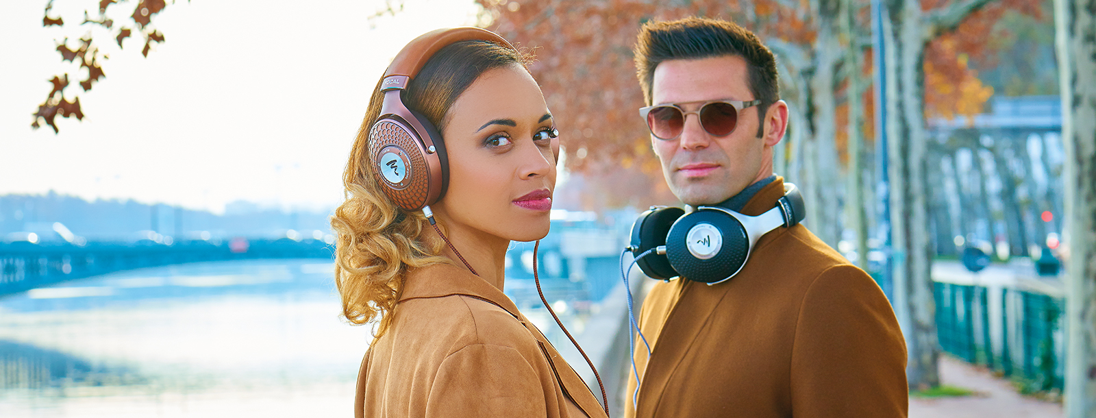 man and woman wearing Focal Stellia headphones on riverbank