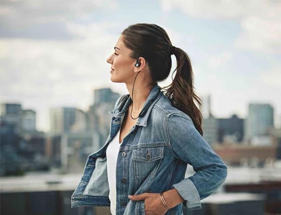 Woman wearing Sennheiser IE-80S BT headphones in the city