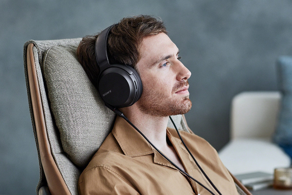 man wearing MDR-Z7M2 headphones, relazing in chair