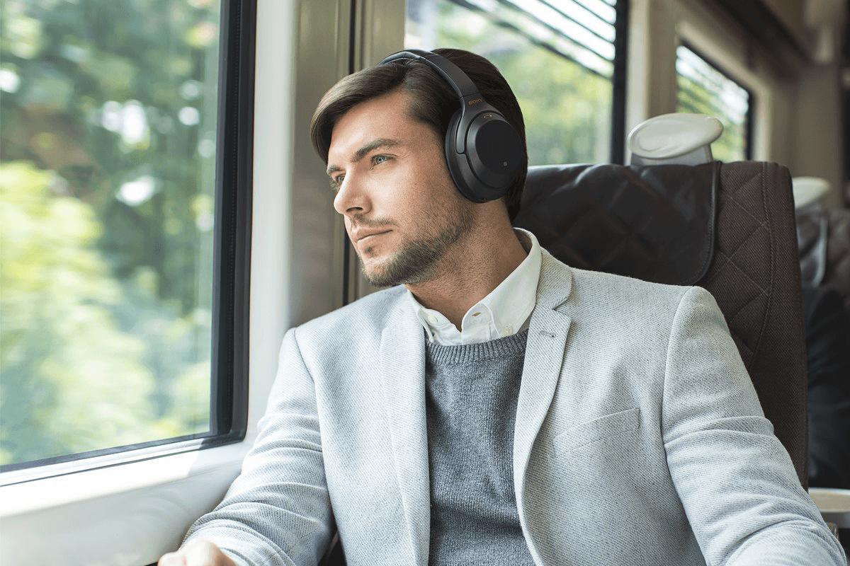Man wearing Sony WH-1000XM3 headphones on train