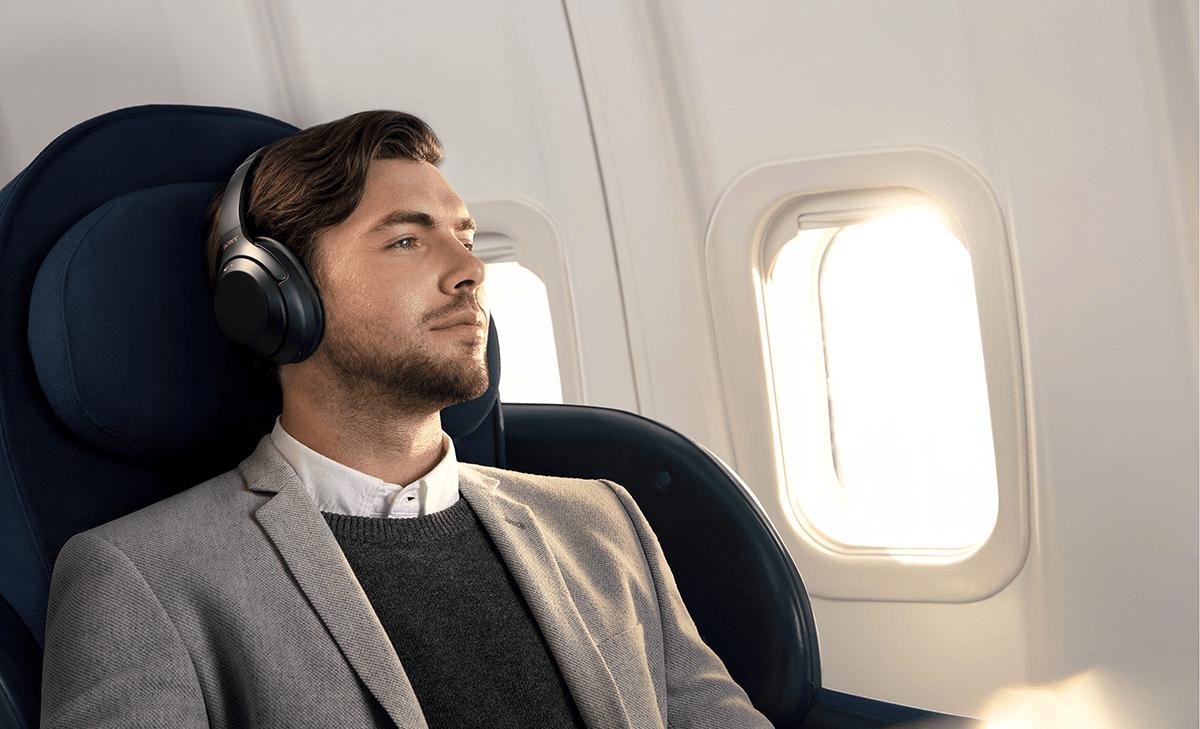 man on plane wearing Sony WH-1000XM3 headphones
