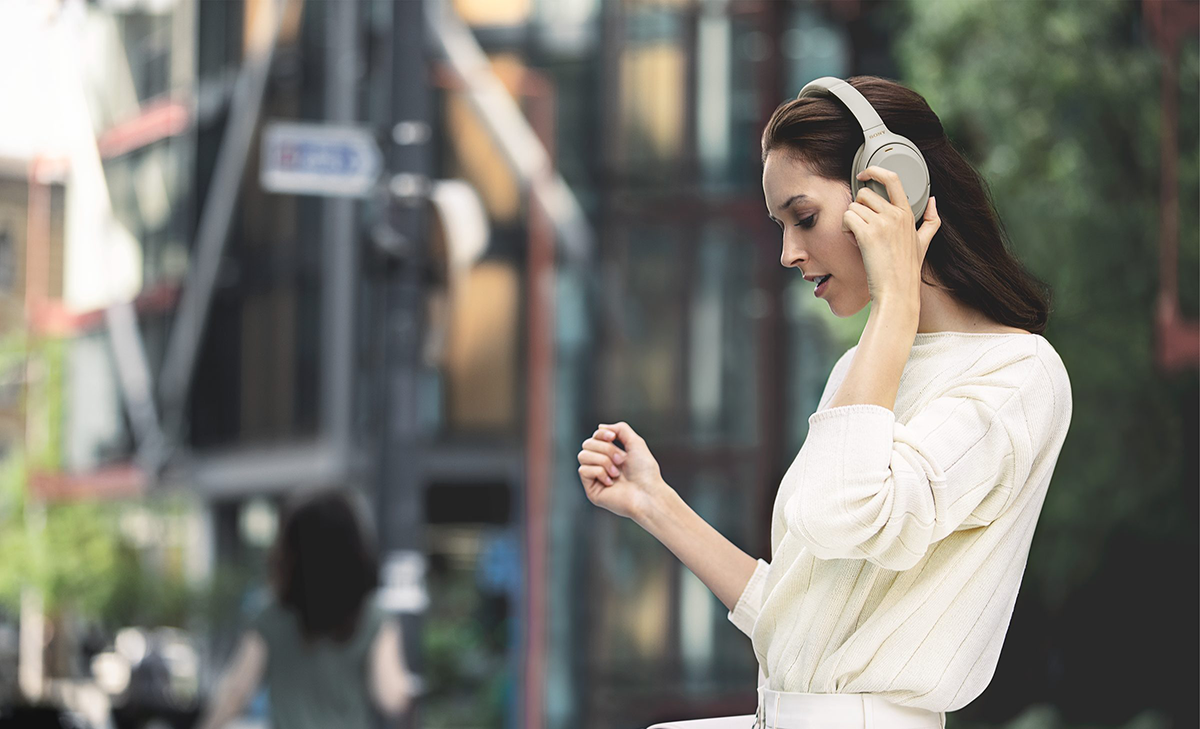 woman wearing Sony WH-1000XM3 headphones on street