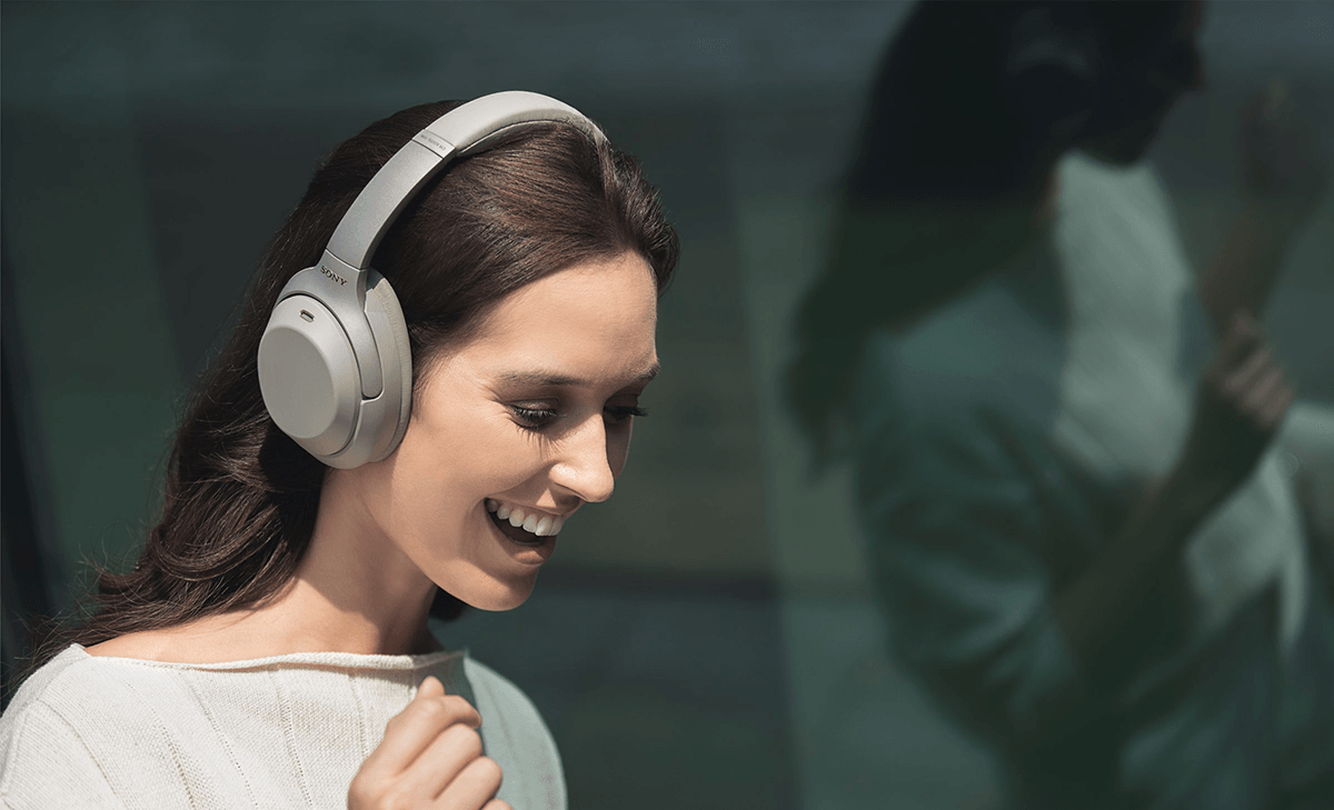 woman talking with Sony WH-1000XM3 headphones