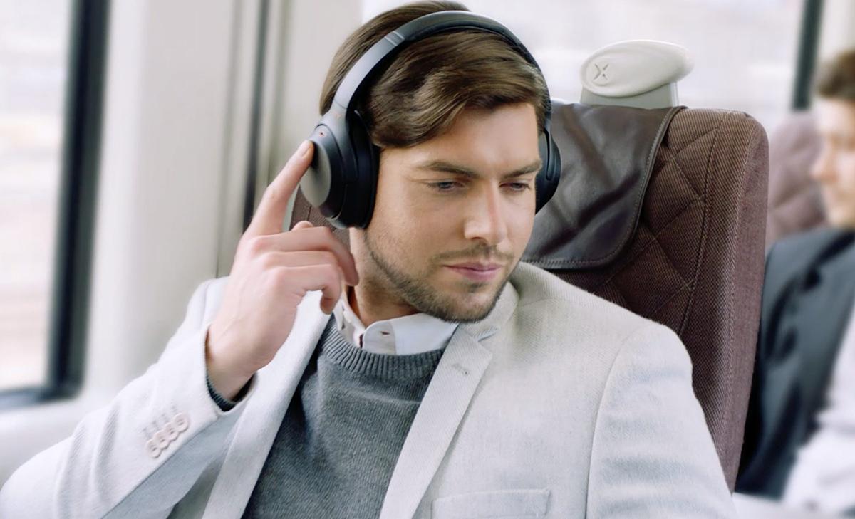 Man on train wearing Sony WH-1000XM3 headphones