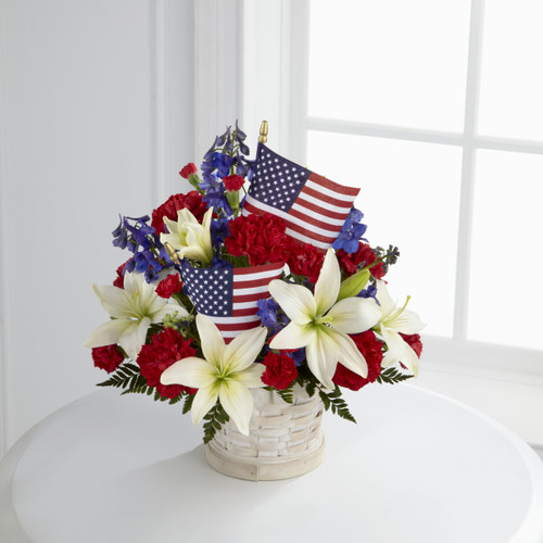 TheAmerican Glory Bouquet bursts with patriotic pride and heartfelt beauty. Blue delphinium, bright red carnations and mini carnations and brilliant white Asiatic lilies create a spectacular display arranged amongst American Flags in a round whitewas