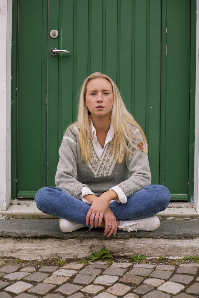 Teenage girl sitting on steps wearing Dale of Norway Alpina ladies sweater in Light Charcoal/Cream 92531-E