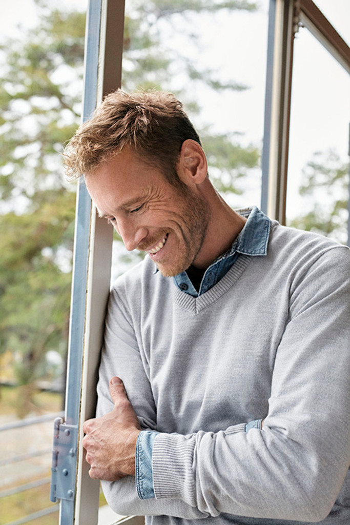 Man by window wearing Dale of Norway's mens Harald sweater in Light Grey Melange, 92412-E