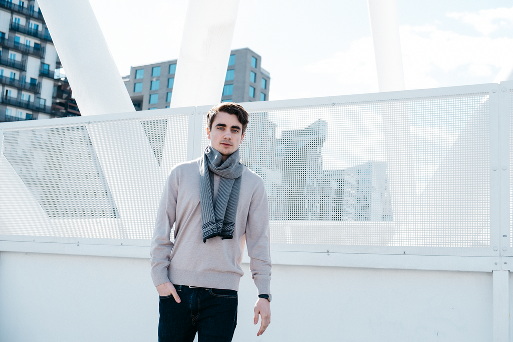 Man on rooftop wearing Dale of Norways mens Harald sweater in Light Grey Melange, 92412-E, with Harald scarf in Navy/Dark Grey, 10981-C