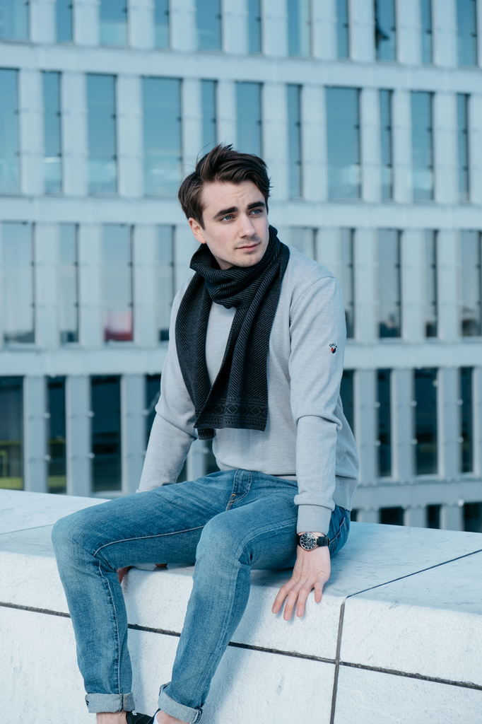 Man sitting on ledge wearing Dale of Norways mens Harald sweater in Light Grey Melange, 92412-E, with Harald scarf in Navy/Dark Grey, 10981-C