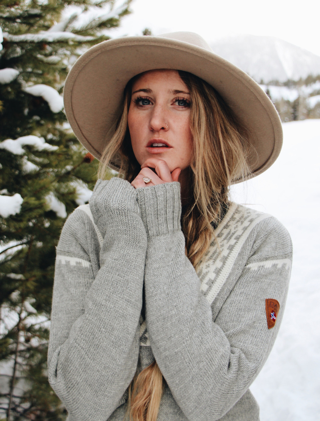 Woman in winter wonderland wearing Dale of Norway Alpina ladies sweater in Light Charcoal/Cream 92531-E