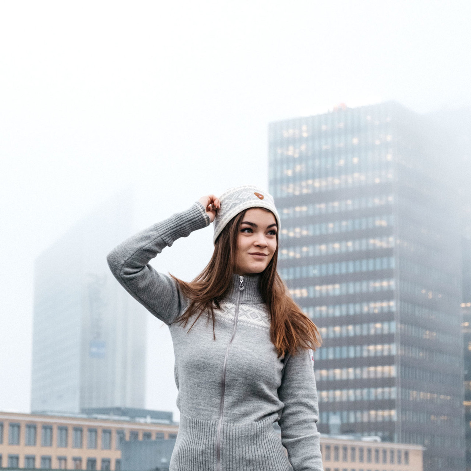 Woman on Oslo rooftop wearing Dale of Norway Hemsedal ladies cardigan in Light Charcoal/Off-White, 82261-T, and Cortina headband in Off White/Light Charcoal, 25014-E
