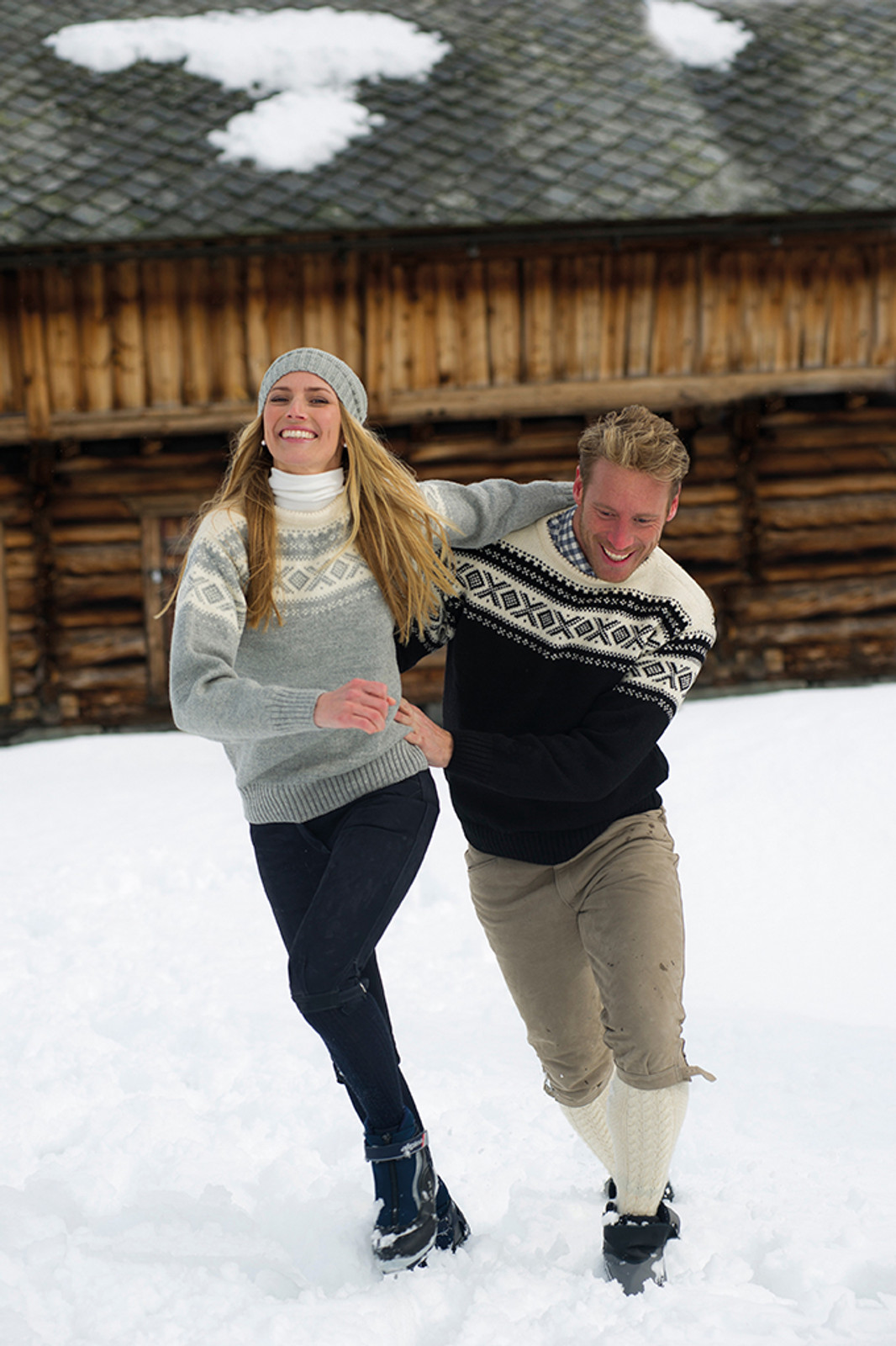 Couple playing in the snow wearing the Dale of Norway Cortina sweater in Light Charcoal/Off White, 92521-E and Navy/Off White, 92521-C