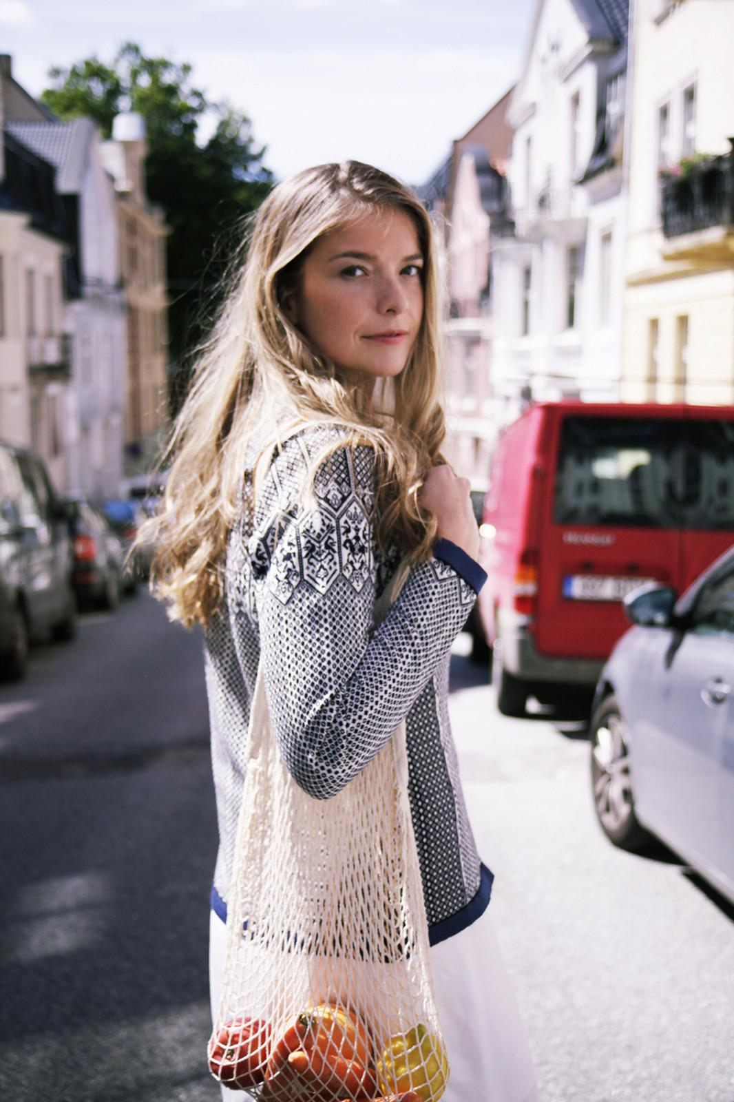 Model walking downtown wearing Dale of Norway Sigrid ladies cardigan in Navy/Off White/Indigo, 82071-C