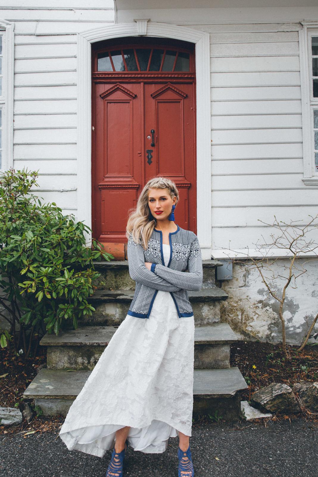 Woman in front of door wearing Dale of Norway Sigrid ladies cardigan in Navy/Off White/Indigo, 82071-C
