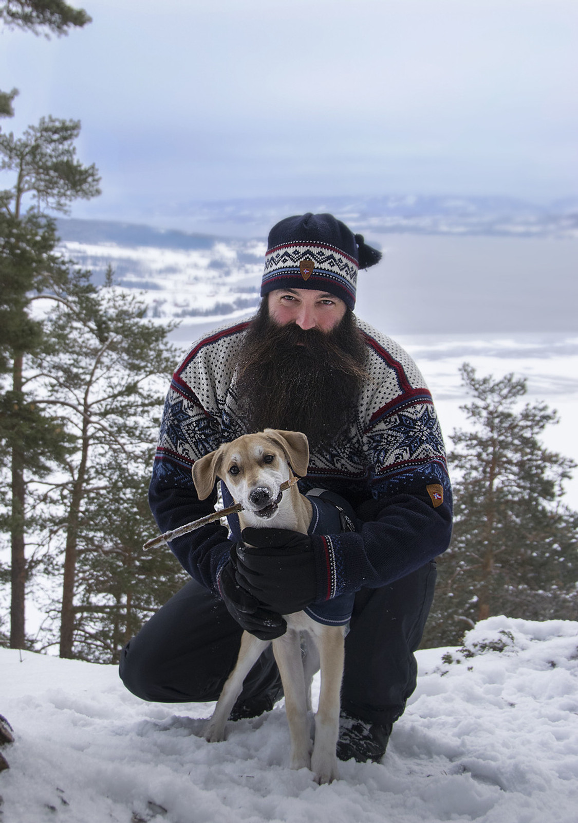 Man with his dog in the woods wearing Dale of Norway's Vail sweater in Midnight Navy/Red Rose/Off White/Indigo/China Blue, 90331-C, and Vail hat in n Navy/Red Rose/Off White/Indigo, 40331-C