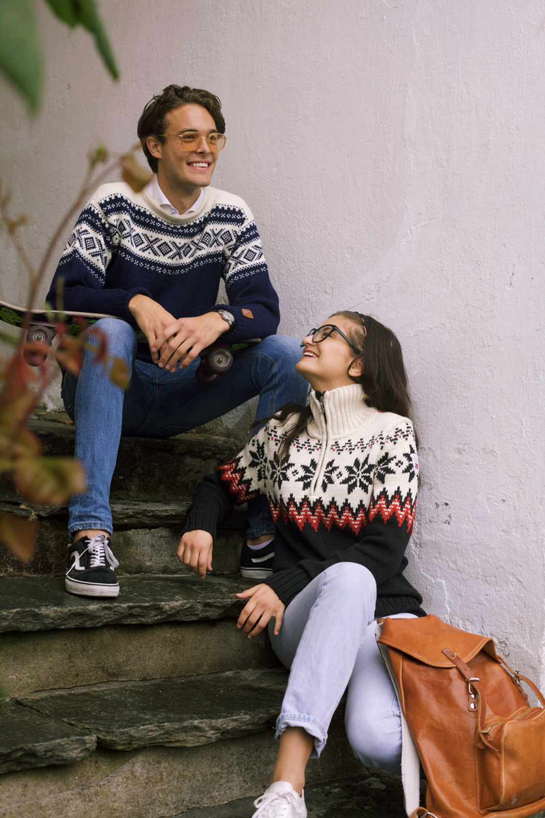 Woman wearing Dale of Norway Myking Ladies Sweater in Black/Raspberry/Off White, 93011-F, and man wearing Dale of Norway Cortina unisex pullover in Navy/Off White, 92521-C, sitting on stairs.