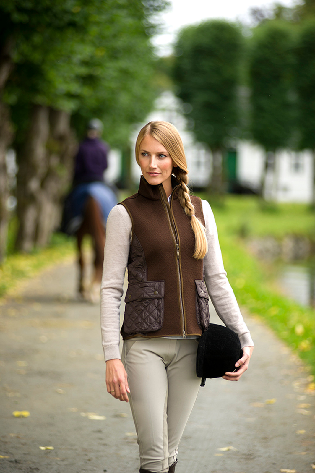 Woman on English horse farm wearing Dale of Norway's Jeger Knitshell ladies vest in Mocca, 85041-R, leading a horse.