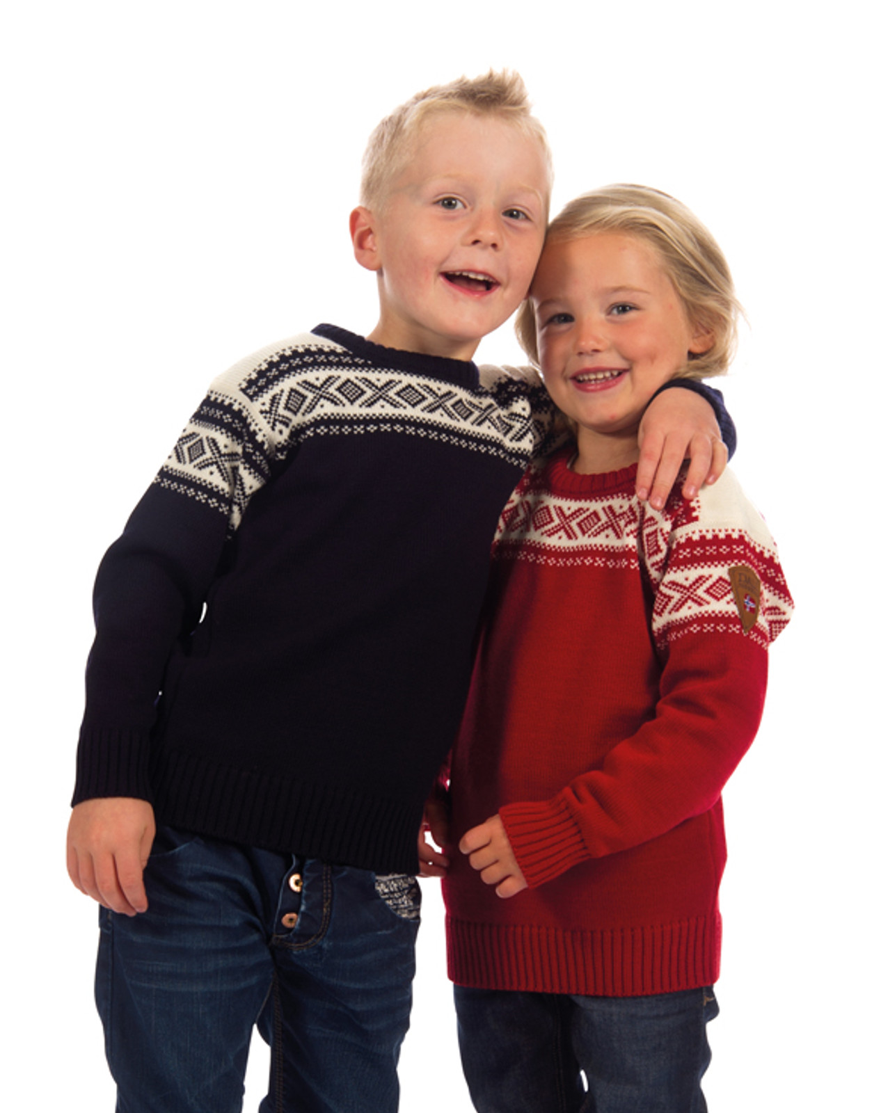 Children showing the different colors of the Dale of Norway Cortina kids sweater. The colors are Raspberry/Off White, 92991-B, and Navy/Off White, 92991-C