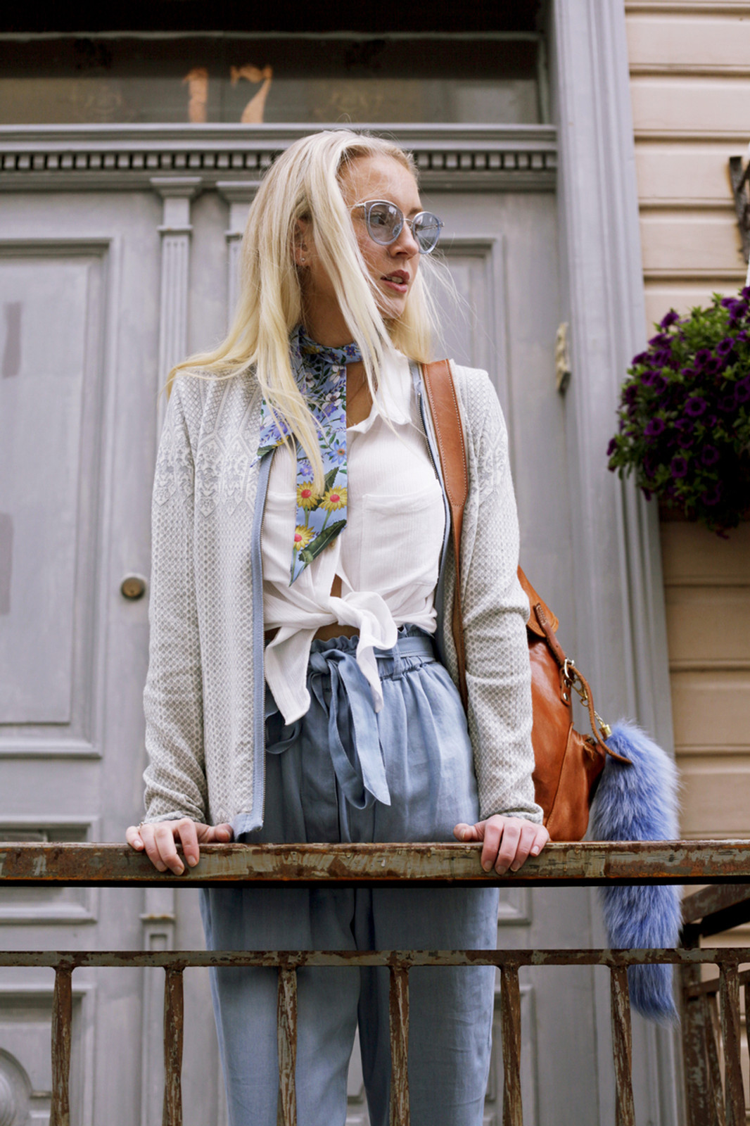 Woman by rail wearing Dale of Norway's Sigrid Ladies Cardigan in Grey Mel/Off White/Ice Blue, 82071-E
