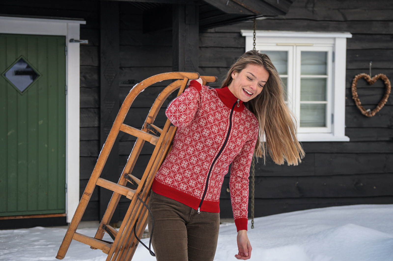 Woman carrying sled and wearing Dale of Norway's Frida cardigan in Raspberry/Off-White/Navy/Metal, 82931-B.