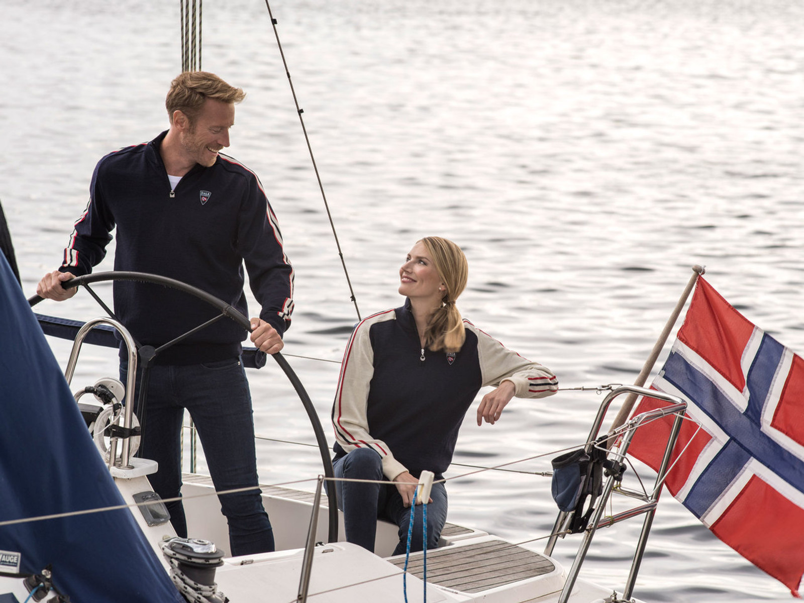 Man and woman sailing wearing Dale of Norway's mens and ladies Flagg sweater in Navy/Raspberry/Off White, 92961-C, and Navy/Off White/Raspberry, 92951