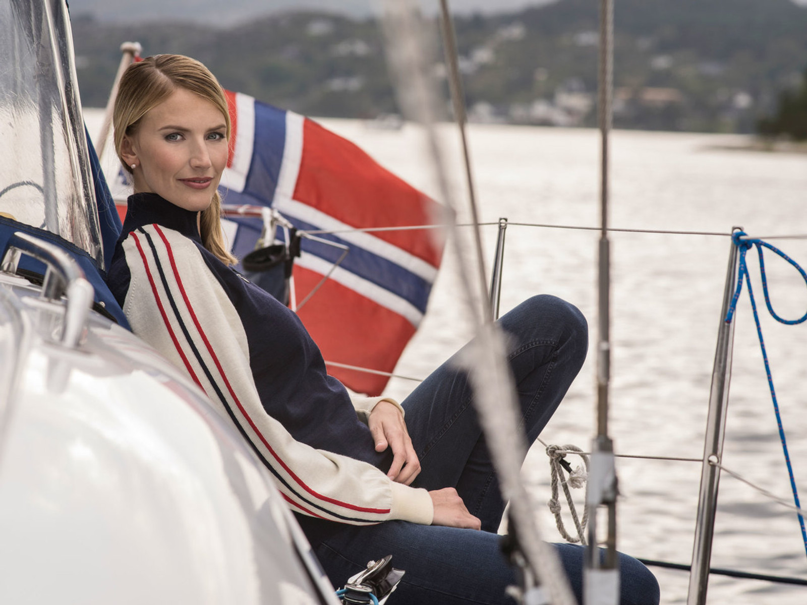 Woman on sailboat wearing Dale of Norway's Flagg ladies sweater in Navy/Off White/Raspberry, 92951-C