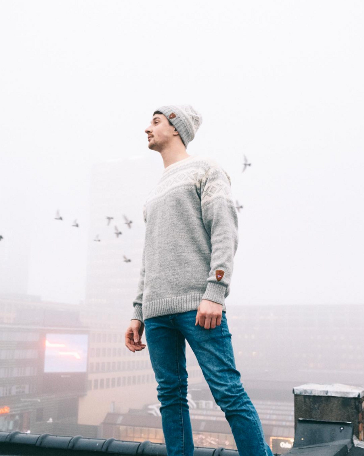 Man on Oslo rooftop wearing Dale of Norway Cortina 1956 sweater in Light Charcoal/Off White, 92521-E, and Cortina hat in Off White/Light Charcoal, 42261-E