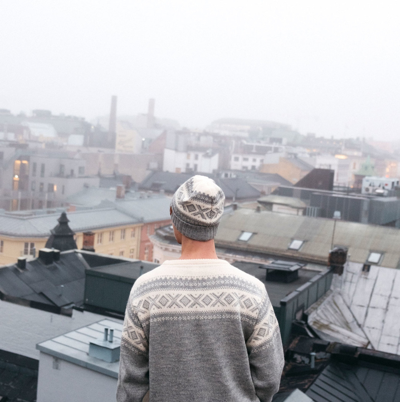 Man looking over Oslo skyline wearing Dale of Norway Cortina 1956 sweater in Light Charcoal/Off White, 92521-E, and Cortina hat in Off White/Light Charcoal, 42261-E