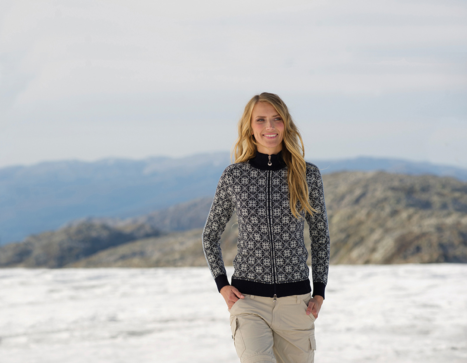 Woman in snow wearing Dale of Norway's Frida ladies cardigan in in Navy/Off-White/Grey Mel/Ice Blue, 82931-C,