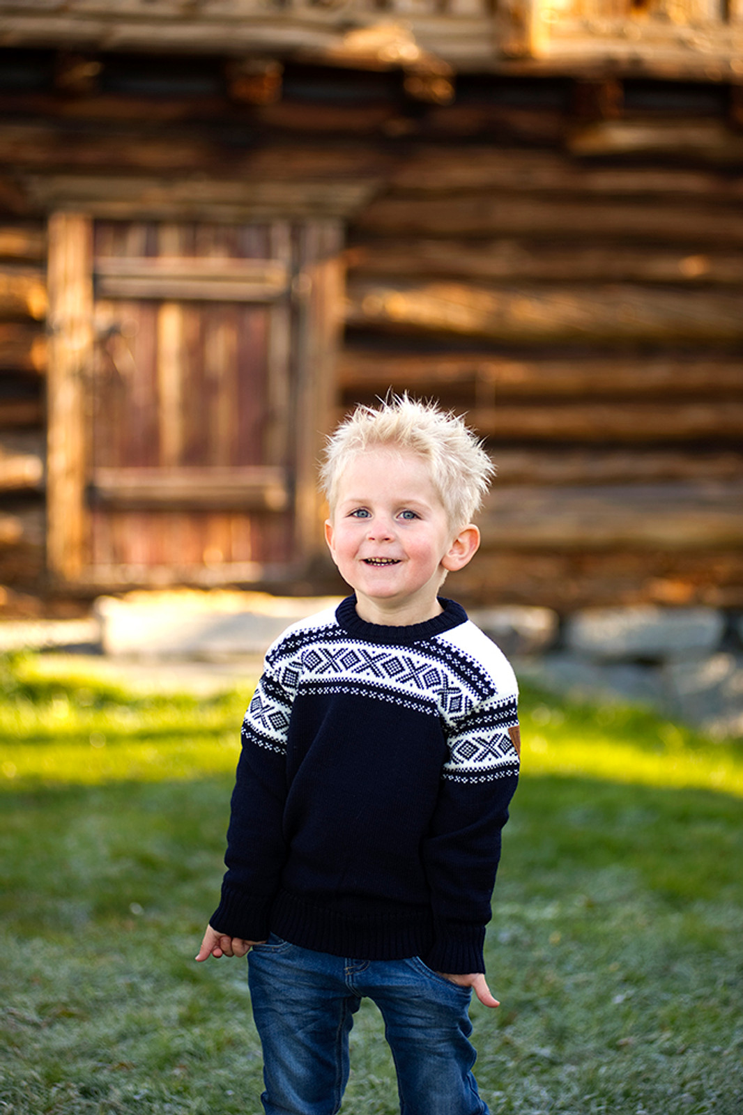 Child in front of log cabin wearing Dale of Norway, Cortina kids sweater in Navy/Off White, 92991-C