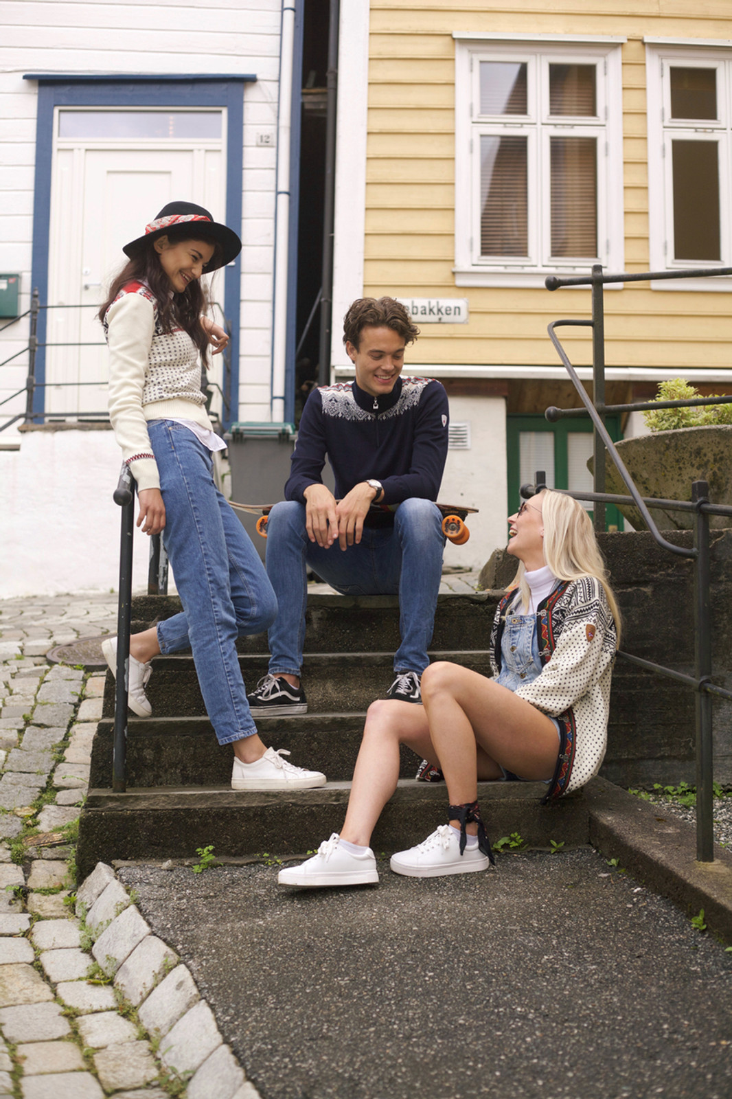 Group of friends wearing Dale of Norway mens Fiemme Sweater in Dark Charcoal/Grau Vig/Raspberry/Off White, 93421-T, new unisex Setesdal cardigan in Off White/Black, 83291-A, and Garmisch ladies sweater in Off White/Navy/Raspberry, 92601-A