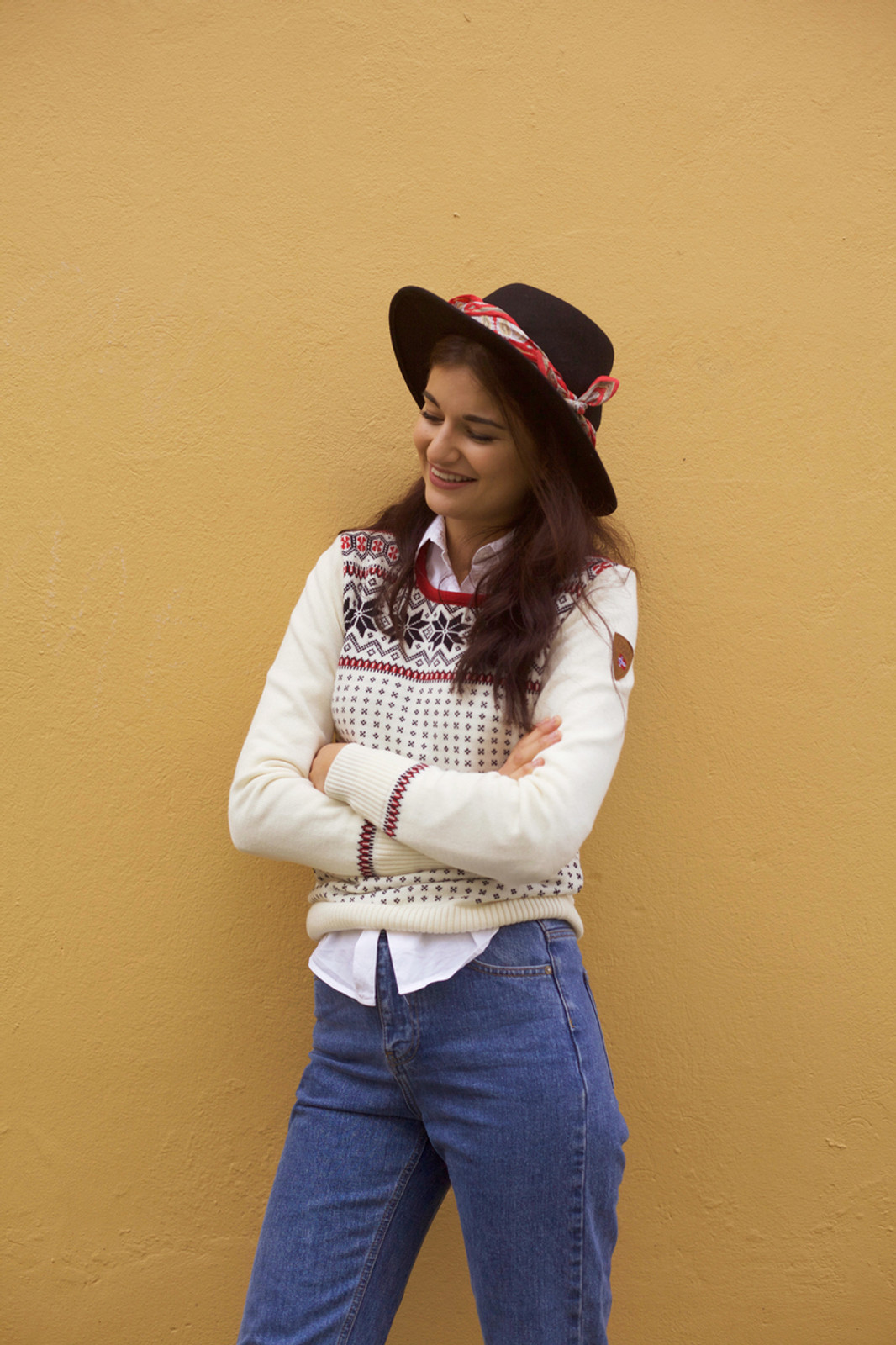Woman standing against wall wearing Dale of Norway Garmisch ladies sweater in Off White/Navy/Raspberry, 92601-A