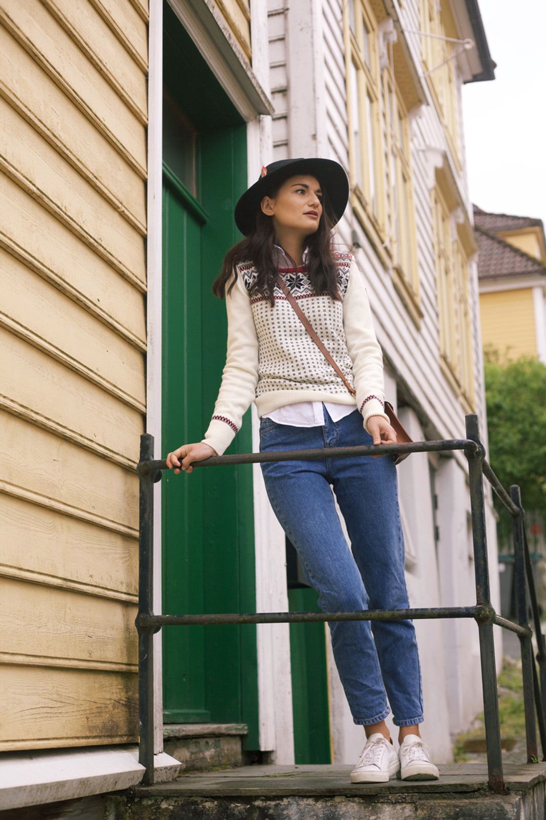 Woman leaning against stairs wearing Dale of Norway Garmisch ladies sweater in Off White/Navy/Raspberry, 92601-A