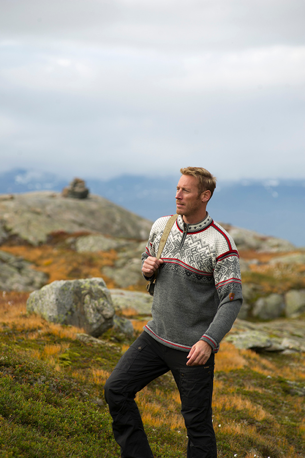 Man standing in field wearing a Dale of Norway unisex Vail sweater in Smoke/Raspberry/Off White/Dark Charcoal/Light Charcoal, 90331-T