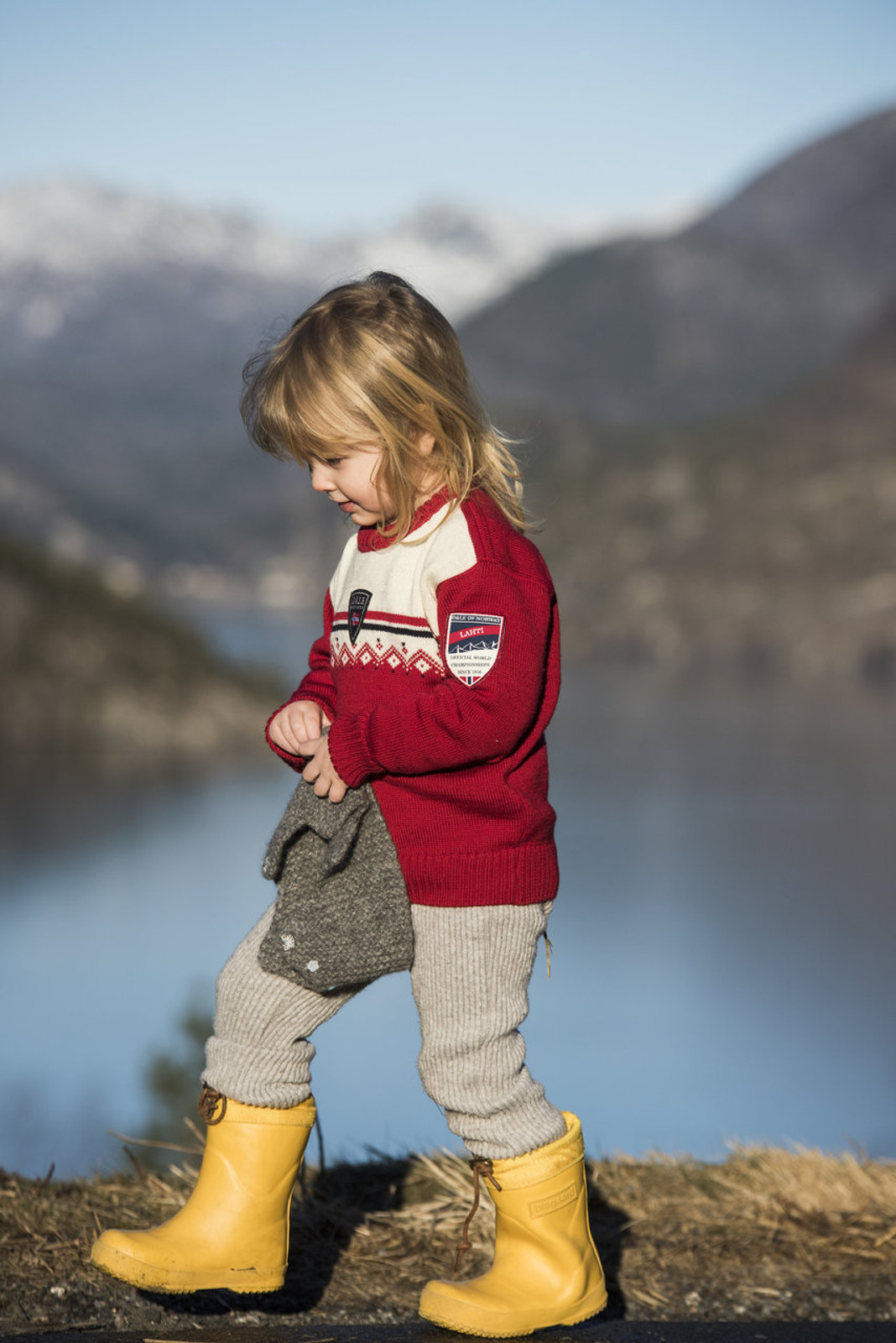 Young Girl walking by lakeside wearing Child wearing Dale of Norway, Lahti childrens sweater in Raspberry/Off White/Navy, 93311-B