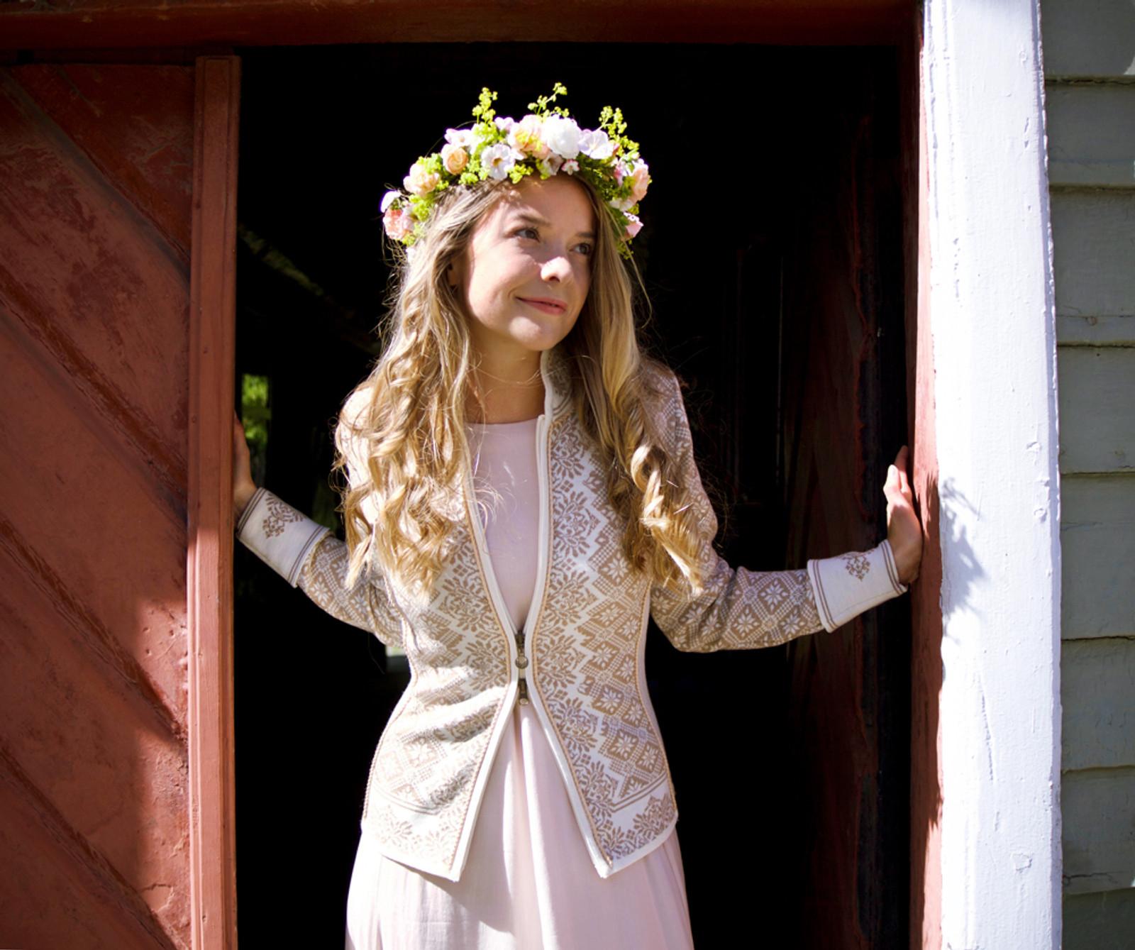 Woman in doorway modeling Dale of Norway Christiania Ladies Cardigan in Off White/Beige, 81951-P