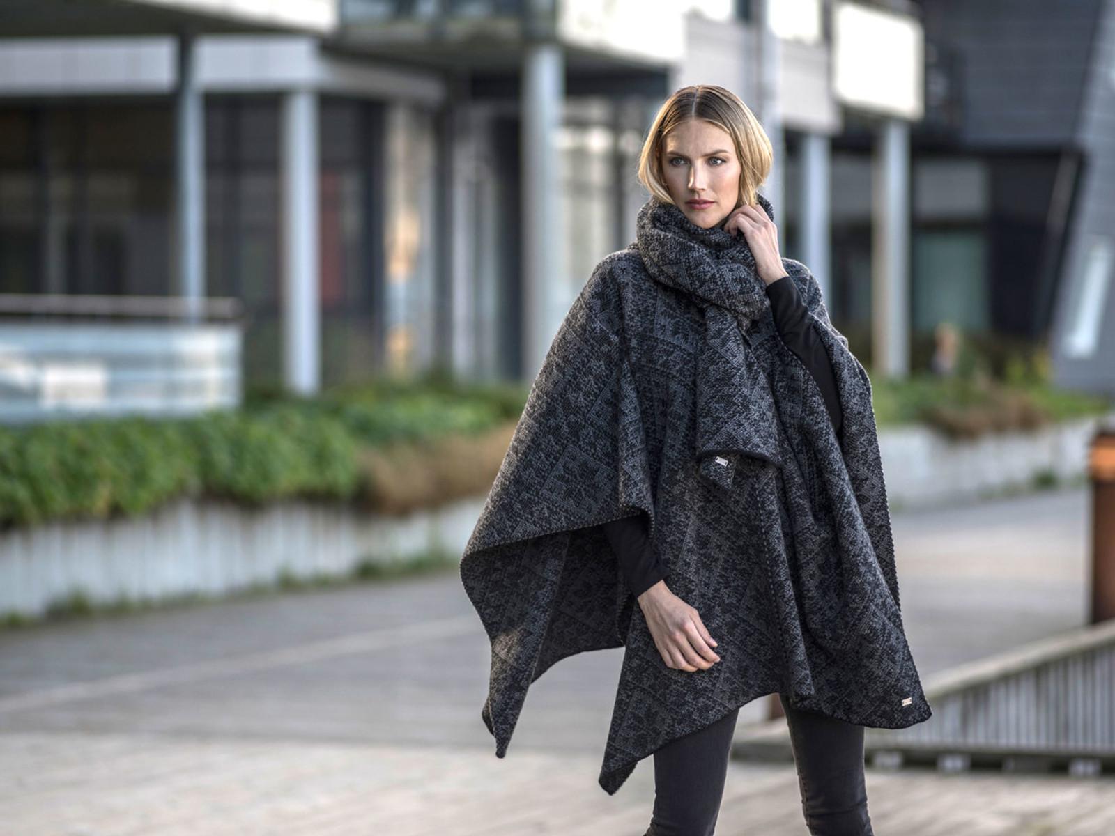 Woman walking downtown wearing Dale of Norway's Rose Ladies Shawl in Black/Smoke, 11651-E, and Rose Scarf in Black/Smoke, 11661-E