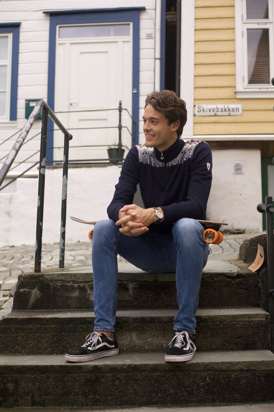 Man sitting on steps wearing Dale of Norway mens' Fiemme sweater in in Navy/Raspberry/Orange Peel/Peacock/Off White, 93421-C