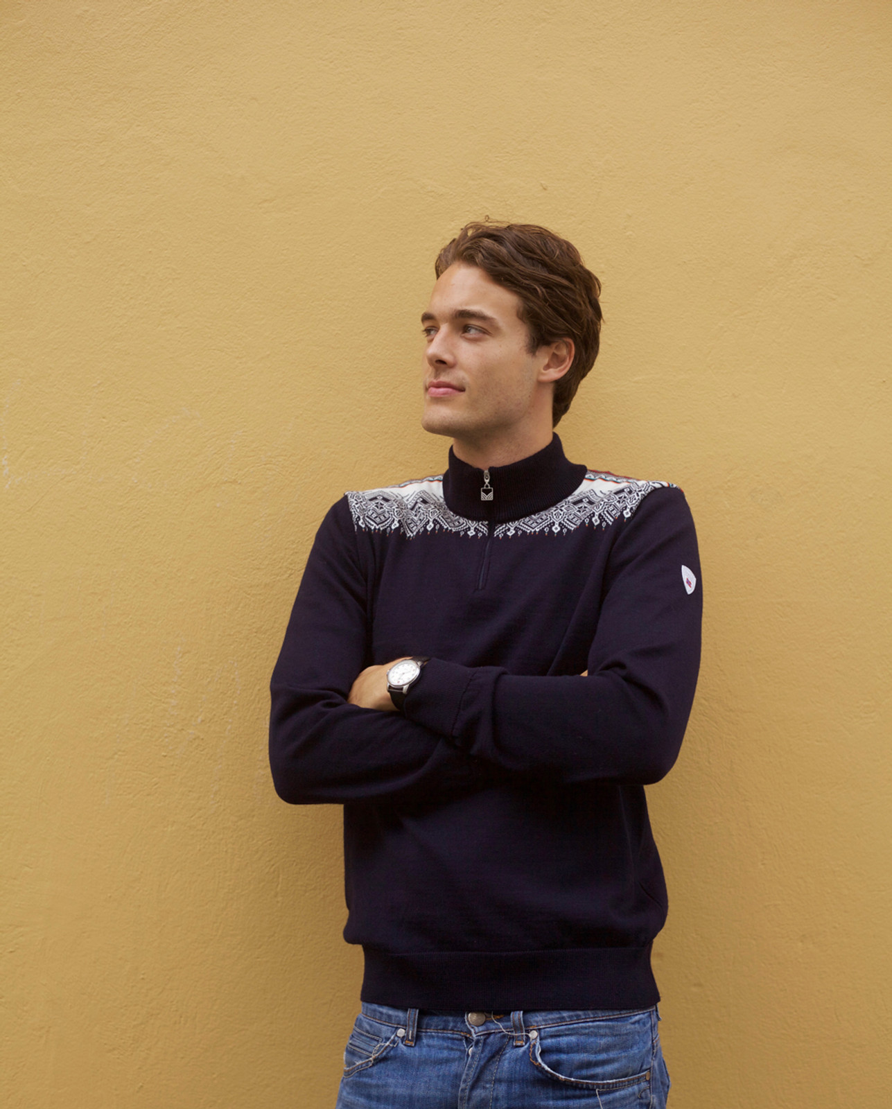 Man standing against wall wearing Dale of Norway mens' Fiemme sweater in in Navy/Raspberry/Orange Peel/Peacock/Off White, 93421-C