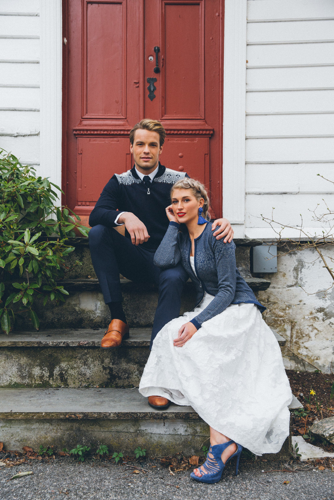 Man and woman in front of door wearing Dale of Norway mens' Fiemme sweater in in Navy/Raspberry/Orange Peel/Peacock/Off White, 93421-C, and Sigrid ladies cardigan in Navy/Off White/Indigo, 82071-C