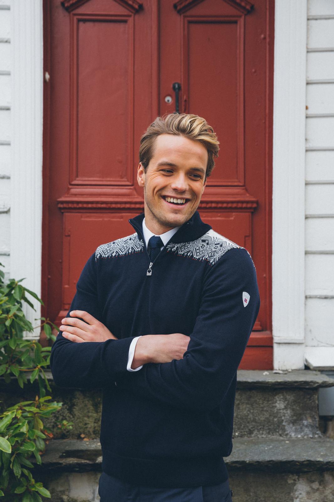 Man in front of door wearing Dale of Norway mens' Fiemme sweater in in Navy/Raspberry/Orange Peel/Peacock/Off White, 93421-C.