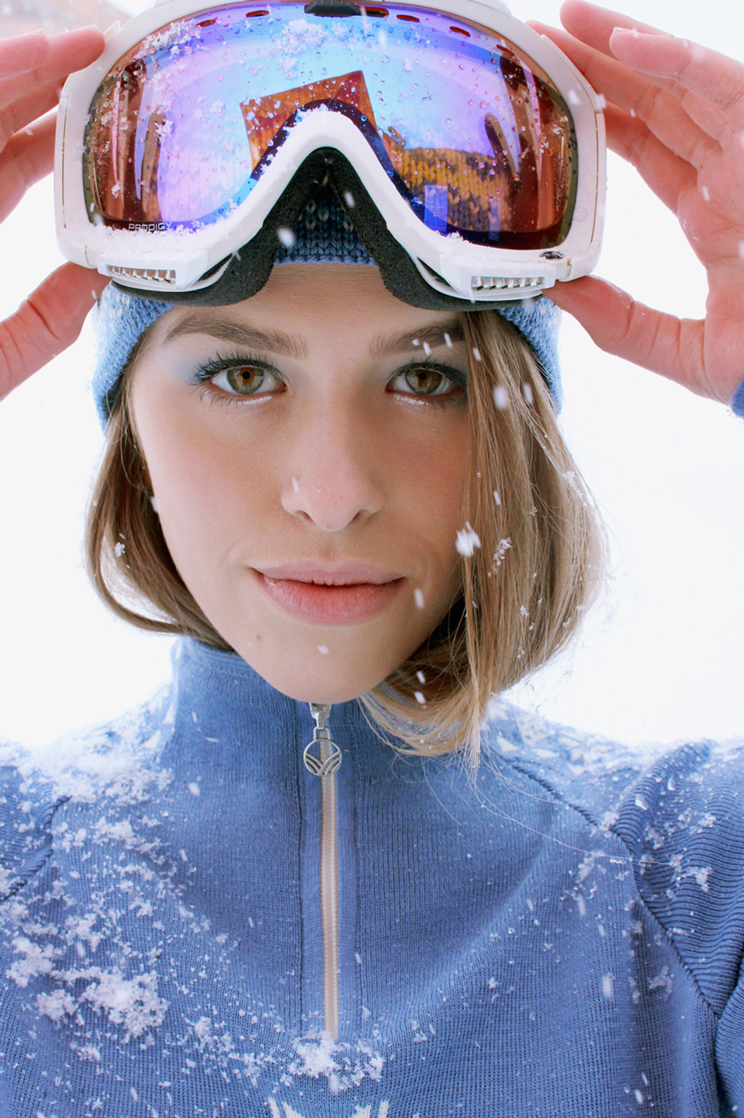 Woman with ski goggles wearing Dale of Norway ladies Geilo pullover in Blue Shadow/Off White, 82311-D