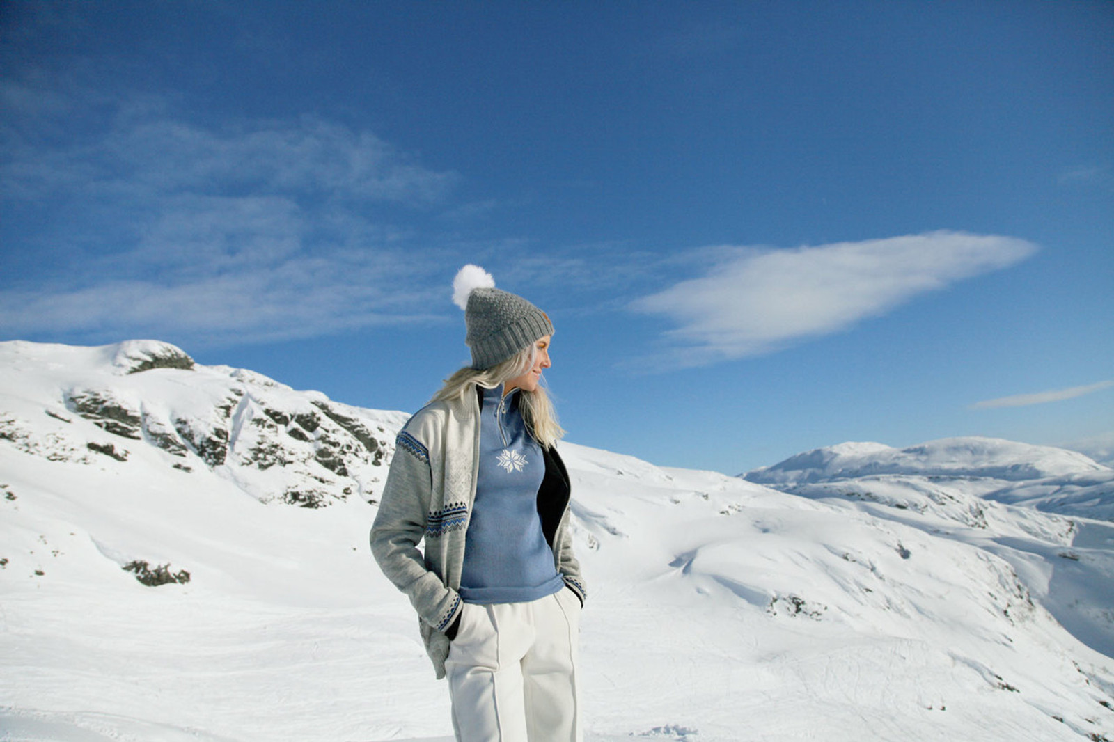Woman wearing Dale of Norway's Glittertind ladies  windstopper jacket in  Light Charcoal/Navy/Cobalt/Off White, 83081-E, Geilo ladies pullover in  Blue Shadow/Off White, 82311-D, and Ulv ladies hat in Smoke, 48011-T